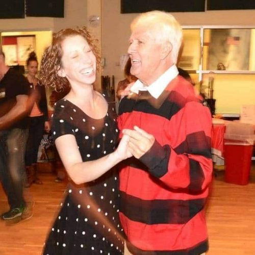 Couple having a blast taking beginner swing dance lessons.